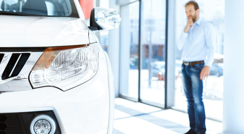 After searching for 'used car dealership near me,' a man is at a car dealership looking at a used car.