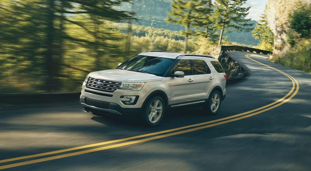 A white 2017 Ford Explorer is driving on a treelined road in Albany, NY.