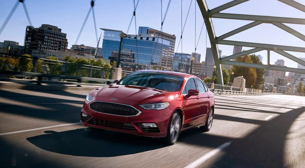 A red 2017 Ford Fusion, a vehicle you may find when searching 'used cars for sale near me', is driving on a highway near Albany, NY.