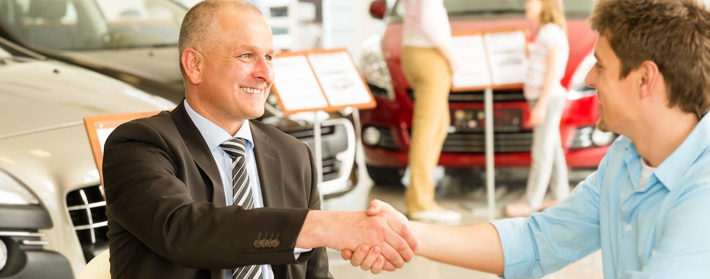 A smiling customer is shaking the hand of a smiling car salesman.