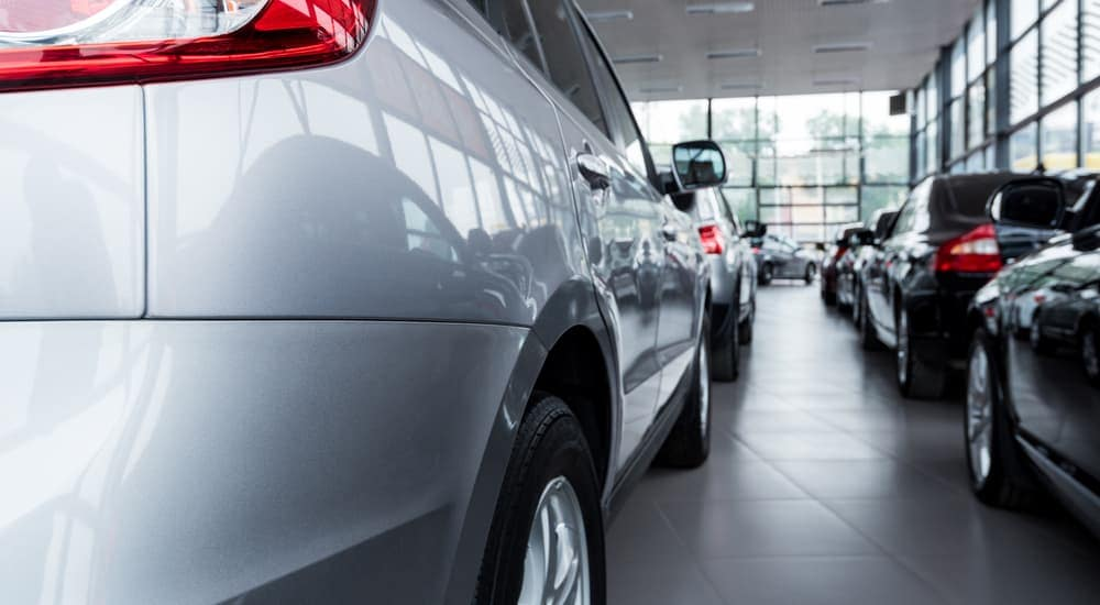 Used cars are shown in a dealerships showroom.