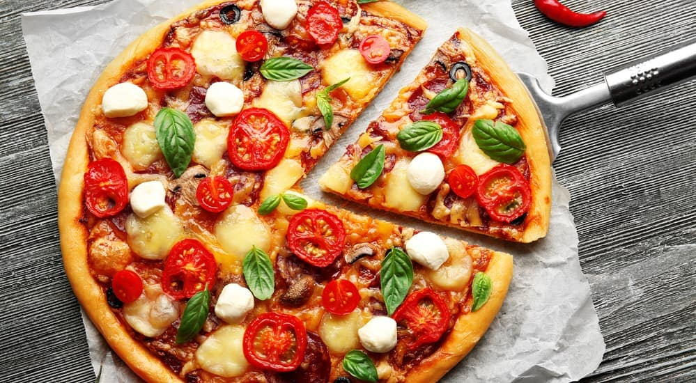 A speciality made pizza, similar to what you could find at a local pizza place in Albany, NY, is shown with cheese, feta, tomato, and more toppings.