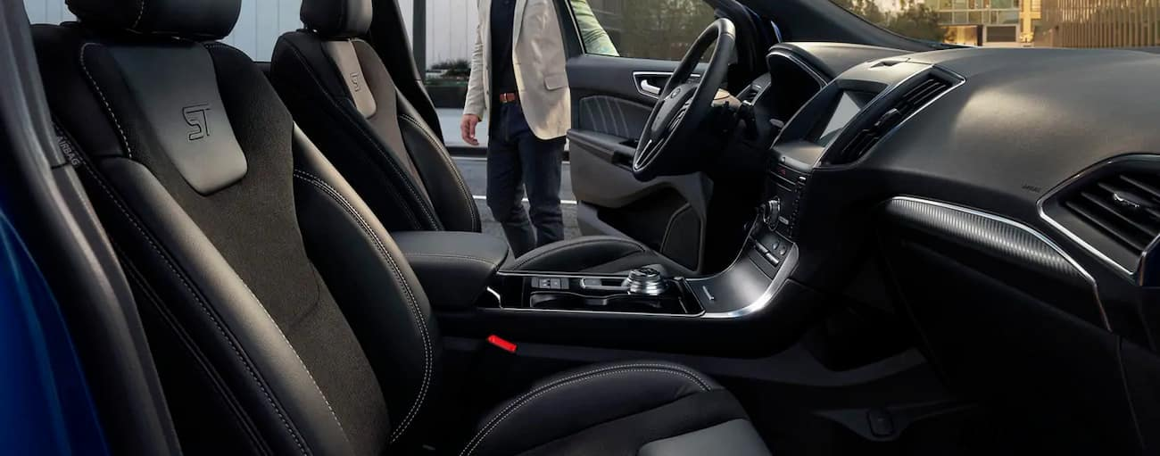 The black interior of the 2019 Ford Edge is shown as the driver door is being opened.