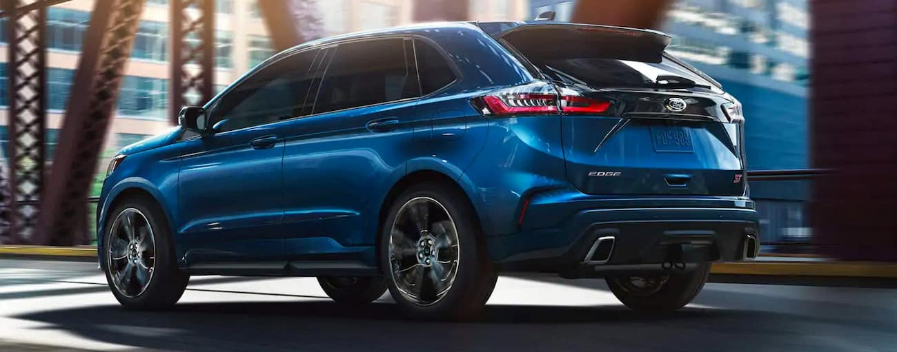 A blue 2019 Ford Edge ST is driving on a bridge near Albany, NY.