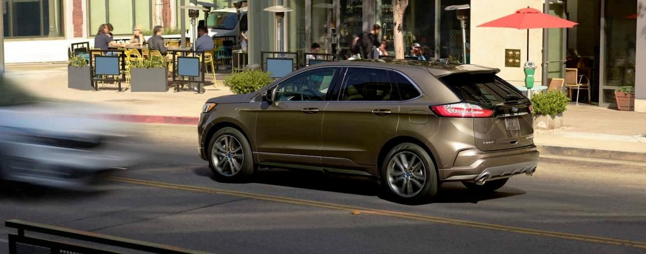 A gold 2019 Ford Edge is driving on a city street.