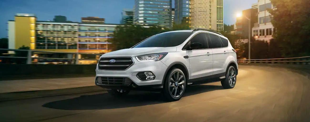 A white 2019 Ford Escape is driving around Albany, NY, at night.