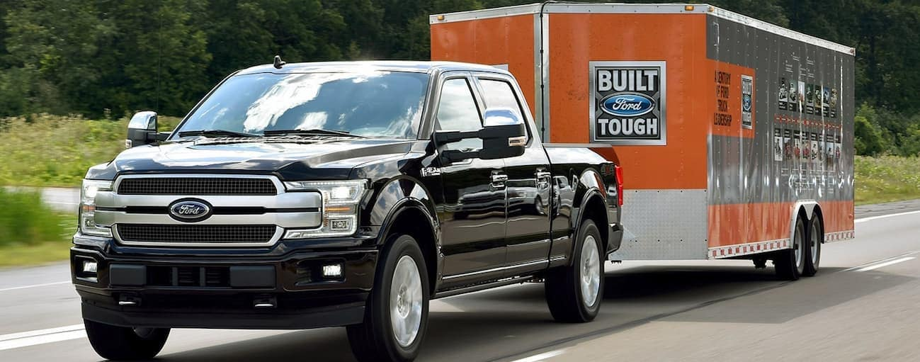 A black 2020 Ford F-150 is towing a large trailer on a treelined road near Albany, NY.