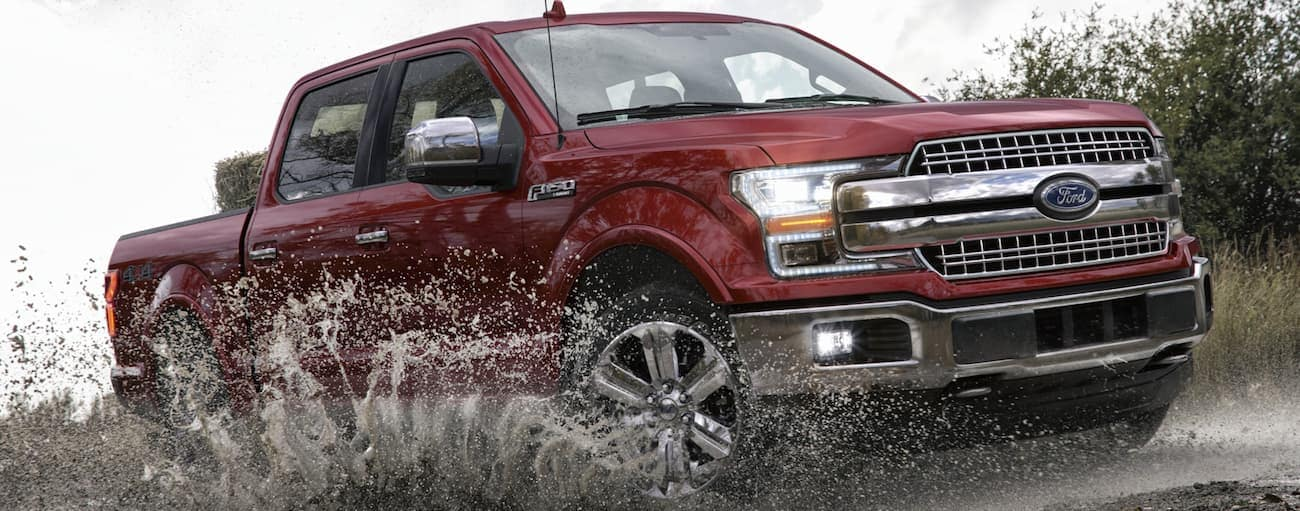 A red 2020 Ford F-150, which wins when comparing the 2020 Ford F-150 vs 2020 Nissan Titan, is driving through a puddle near Albany, NY with dirt and water spraying up.