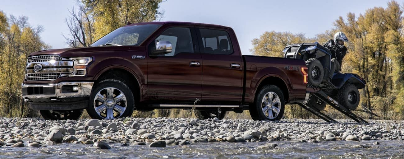 A burgundy 2020 Ford F-150 is parked by a river while a man loads his 4-wheeler.
