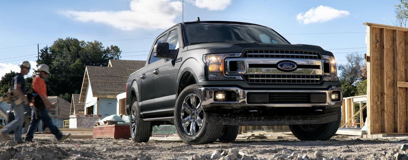 A dark grey 2020 Ford F-150, which wins when comparing the 2020 Ford F-150 vs 2020 Ram 1500, is parked at a construction site.