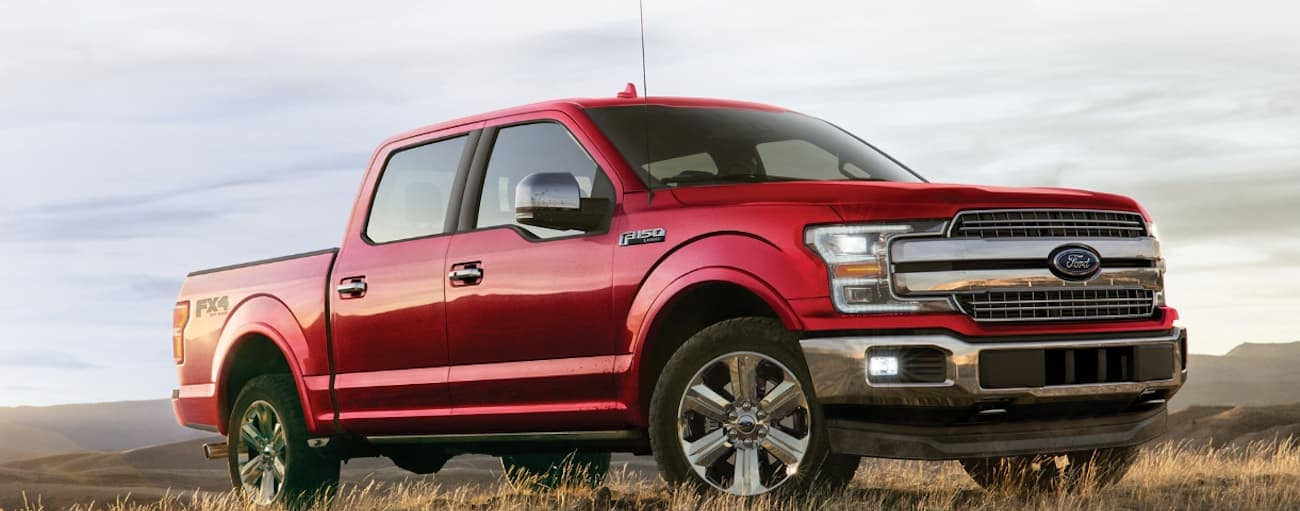 A red 2020 Ford F-150 is parked in a grassy field near Albany, NY.