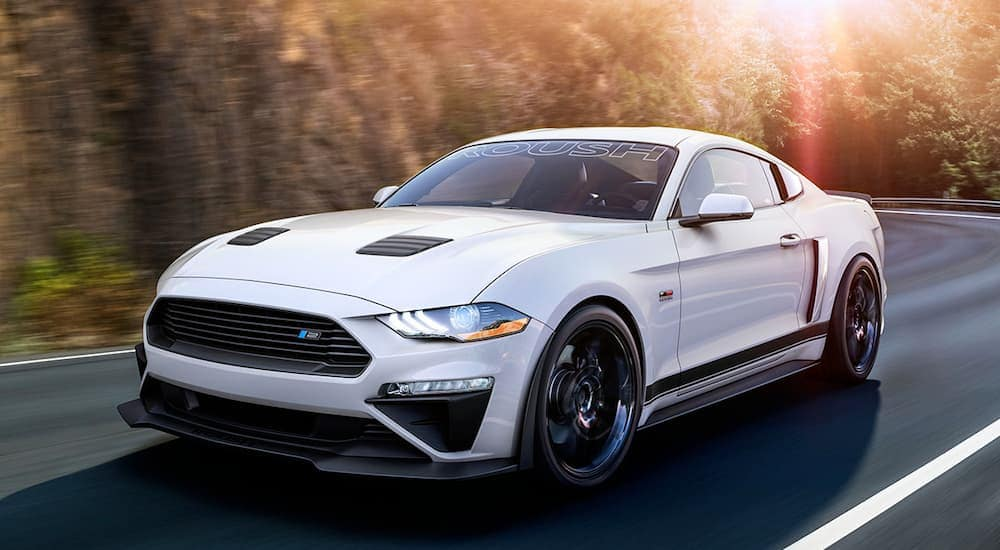A white 2019 Roush Mustang is driving on a highway near Albany, NY, headed to one of the best Ford dealership locations.