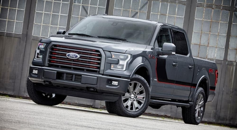 A grey 2016 Ford F-150, which is a popular option among used Ford trucks, is parked in front of a warehouse near Albany, NY.