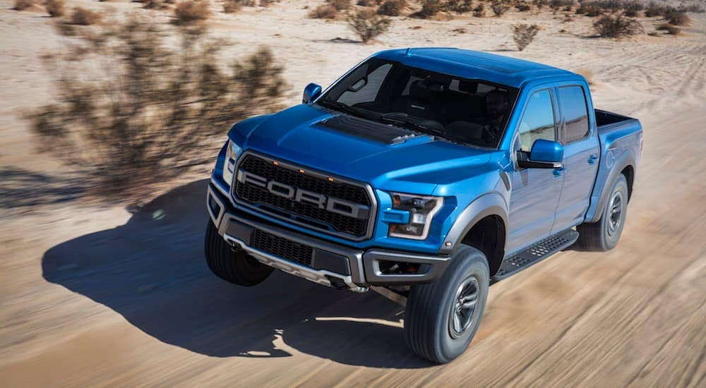 A blue 2018 Ford Raptor is driving down a dirt trail.