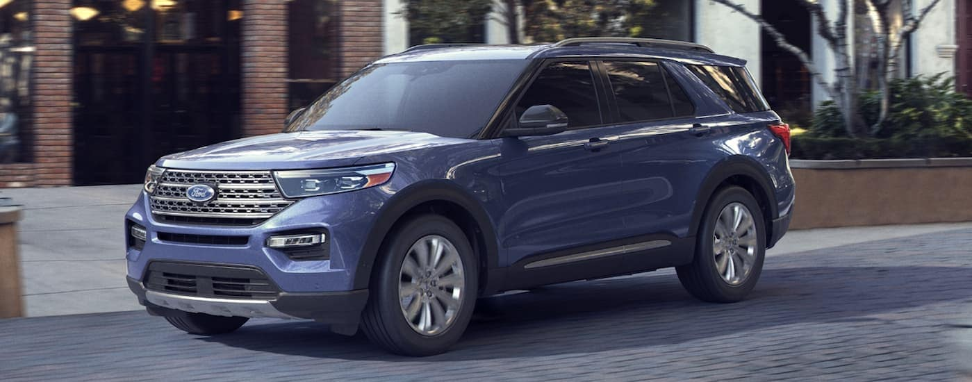 A blue 2020 Ford Explorer, which is a popular option among Ford SUVs, is parked in front of an office building near Albany, NY.