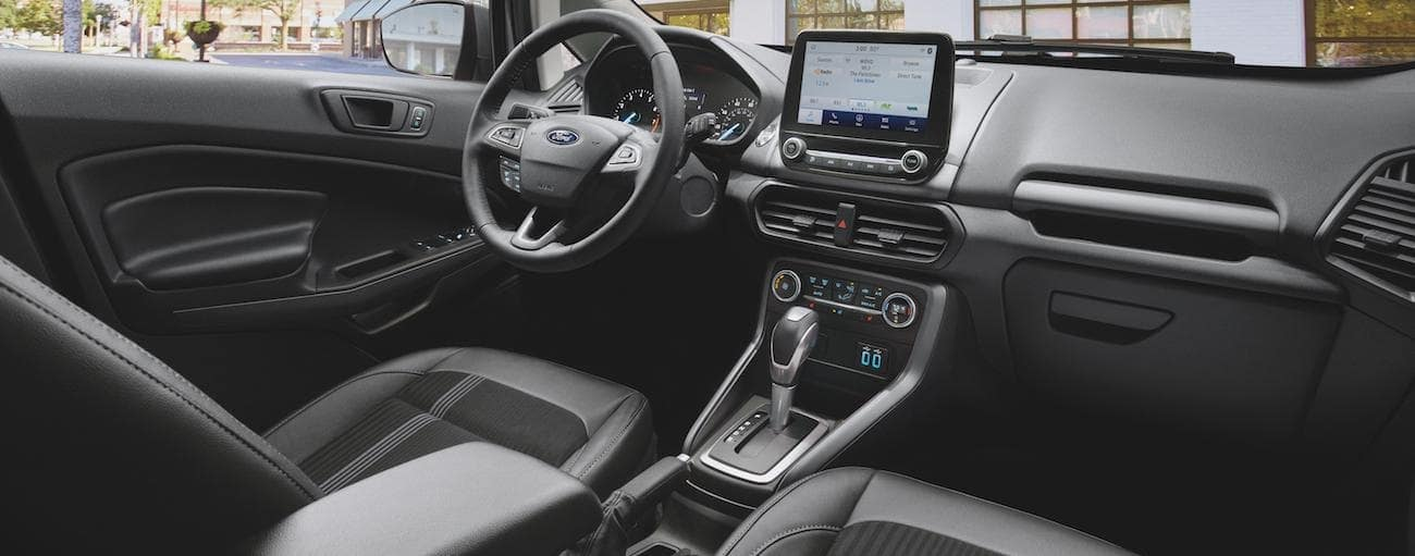 The front black and grey interior of a 2020 Ford Ecosport is shown with an infotainment system and a driver's display.