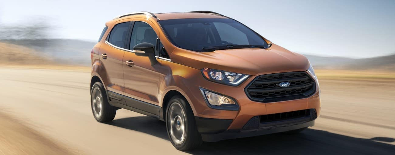 An orange 2020 Ford Ecosport is driving on a dirt road near Albany, NY.