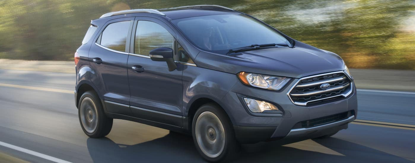 A grey 2020 Ford Ecosport is driving on a treelined road near Albany, NY.