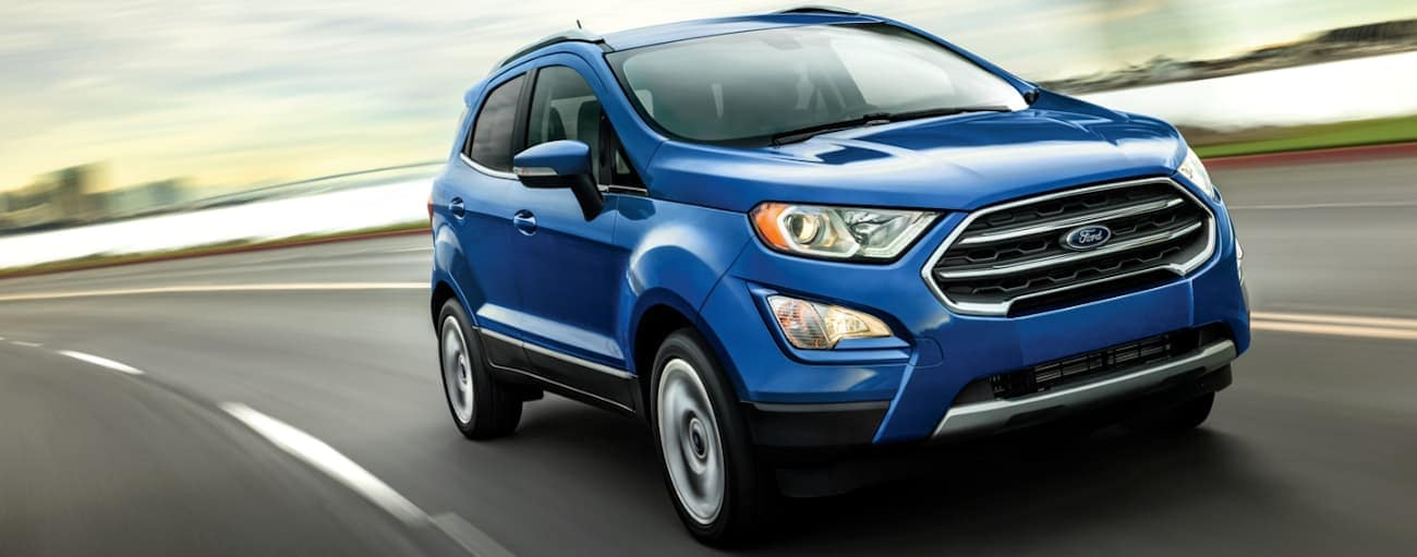 A blue 2020 Ford Ecosport, which wins when comparing the 2020 Ford Ecosport vs 2020 Chevy Trax, is driving on a highway near Albany, NY.