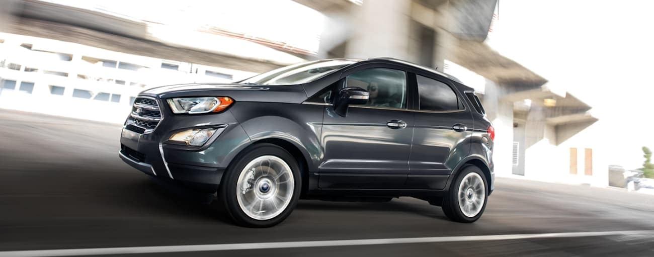 A dark grey 2020 Ford Ecosport is driving with a blurred background.