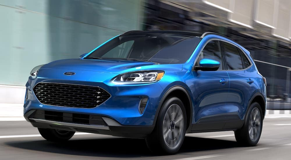 A blue 2020 Ford Escape is driving passed blurry buildings.