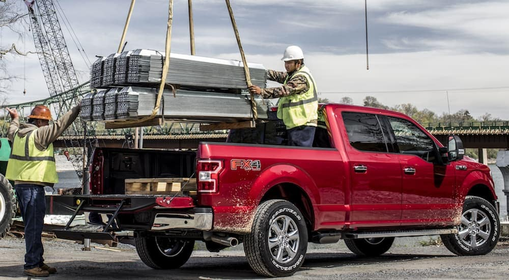 Two construction workers are loading heavy metal pieces into the bed of a red 2020 Ford F-150.