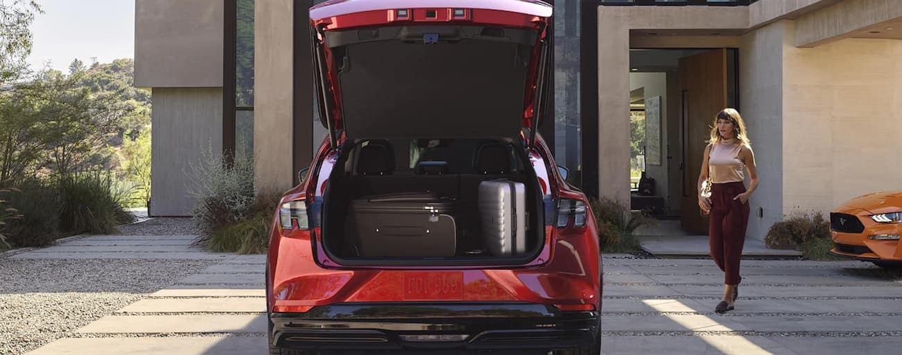 A woman is walking to her red 2021 Ford Mustang Mach-E that has the liftgate open with luggage in the trunk.