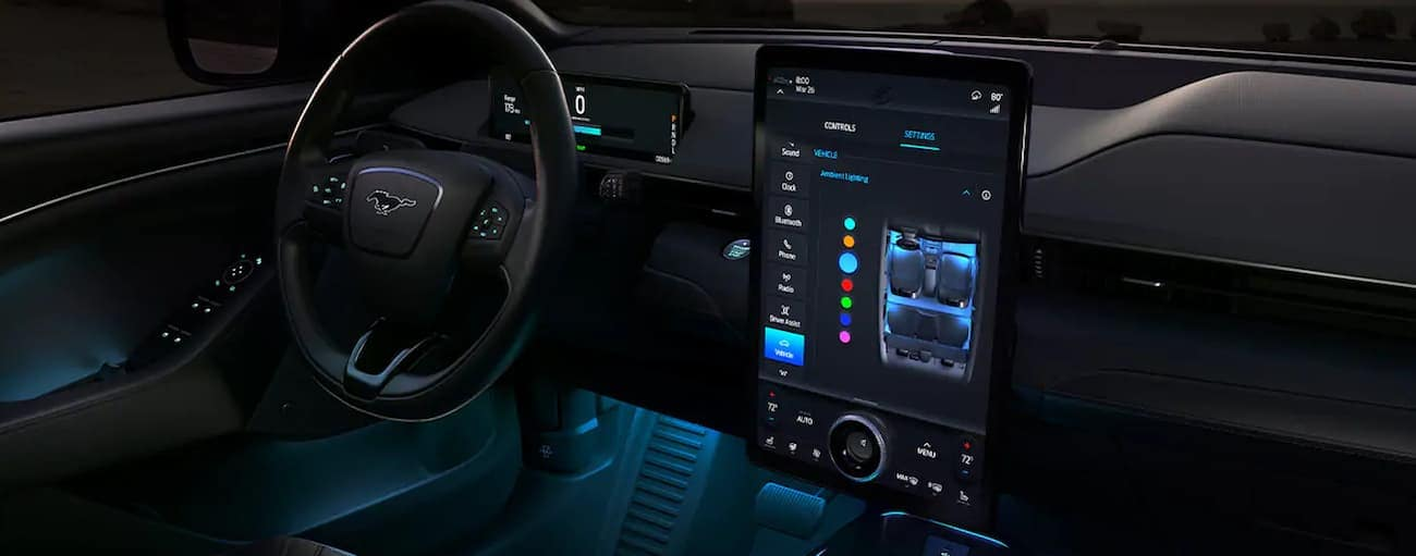 The front black leather interior of a 2021 Ford Mustang Mach-E is shown with blue accent lights and a large infotainment screen.