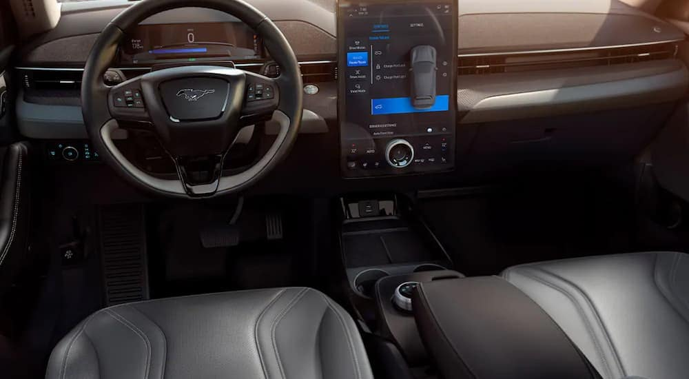 The front black leather interior of a 2021 Mach-E is shown.