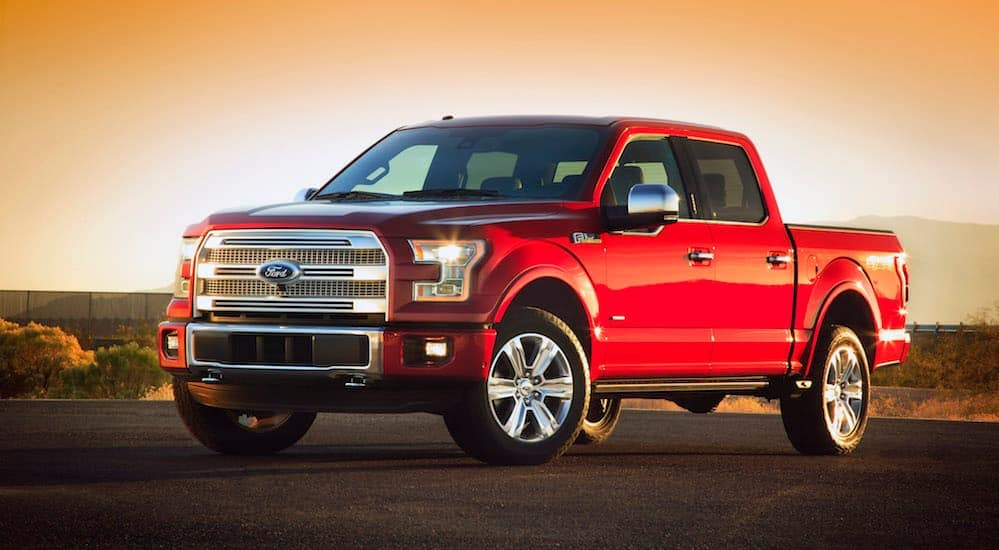 A red 2015 Ford F-150 is parked in an empty parking lot while the sun sets behind it.