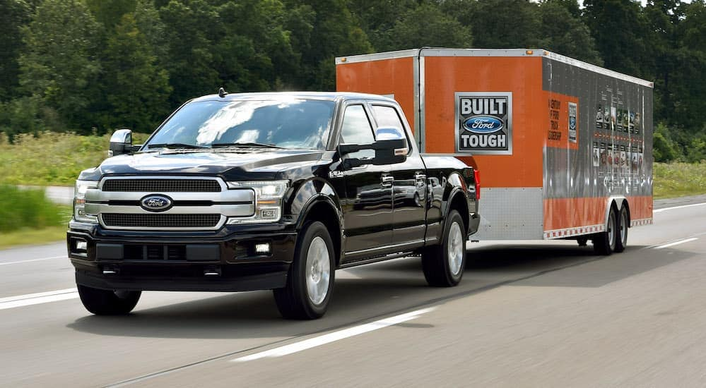 """A black 2018 Ford F-150, which is a popular model when searching for """"used car dealer near me,"""" is towing a large enclosed trailer near Albany, NY."""