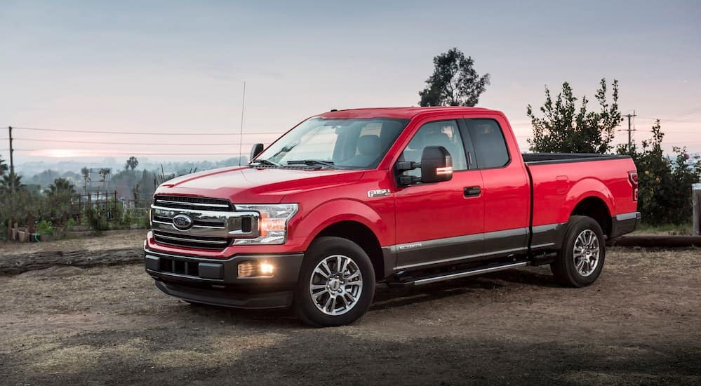 A red 2018 Ford F-150, which is a popular option among used Ford trucks, is parked in a parking lot near Albany, NY.