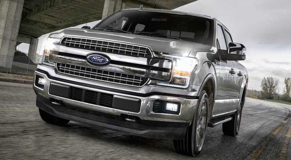 A silver 2018 Ford F-150, which is a popular option among used Ford trucks, is driving under a bridge near Albany, NY.