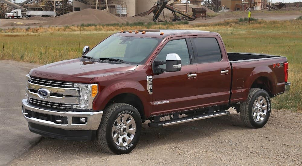 A maroon 2017 Ford Super Duty is parked in front of a job site.