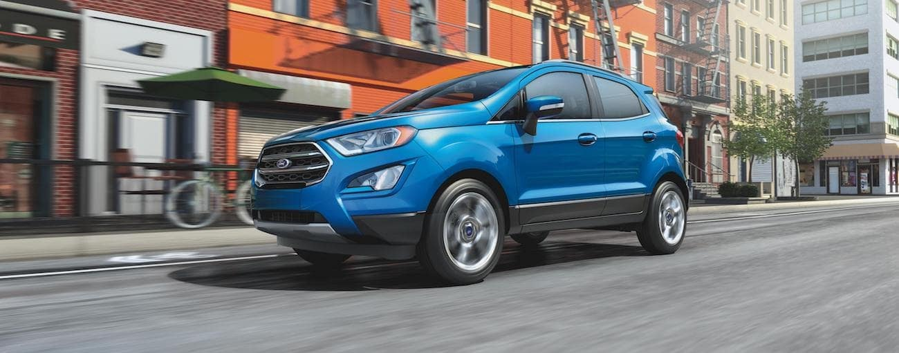 A blue 2020 Ford EcoSport, which wins when comparing the 2020 Ford EcoSport vs 2020 Honda HR-V, is driving past tall brick buildings near Albany, NY.