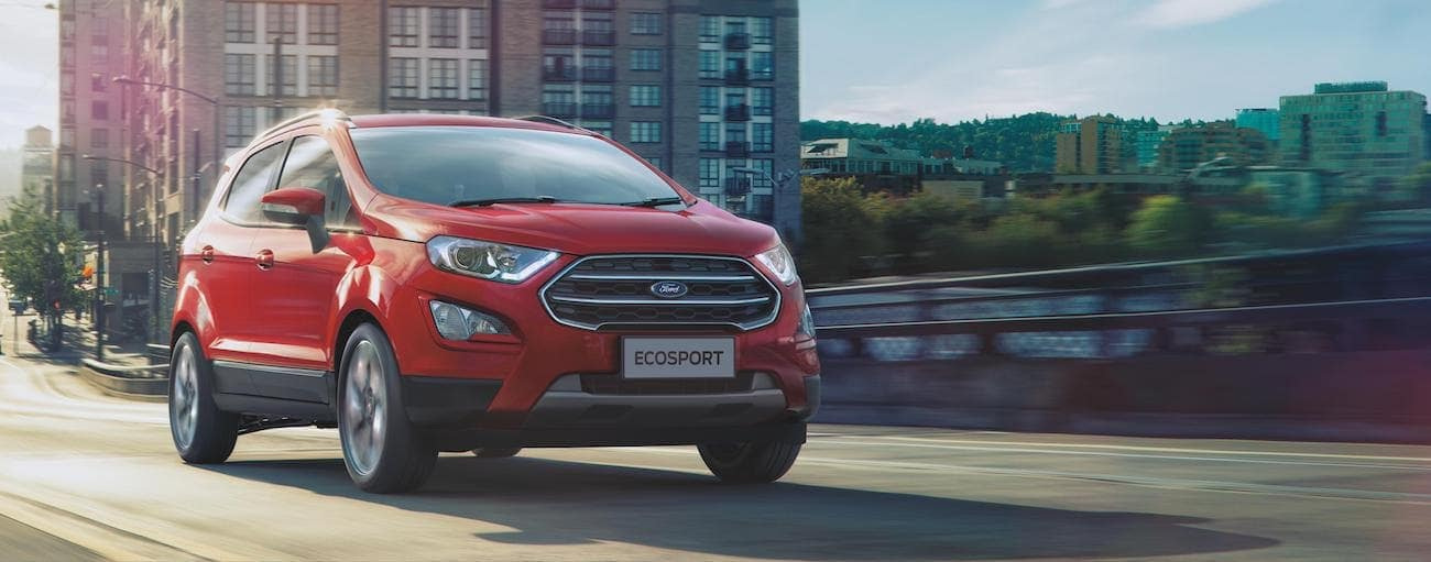 A red 2020 EcoSport is driving on a bridge with tall apartment buildings in the distance.