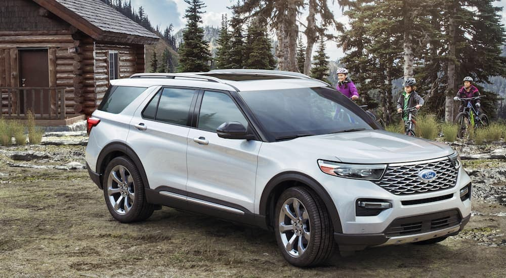 A white 2020 Ford Explorer is parked next to a remote cabin in the Albany, NY, woods.