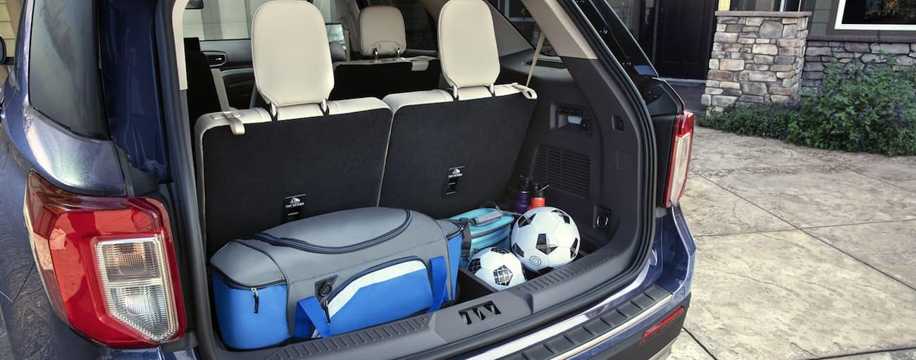 The trunk area behind the third row seats of a 2020 Ford Explorer has football gear in it.
