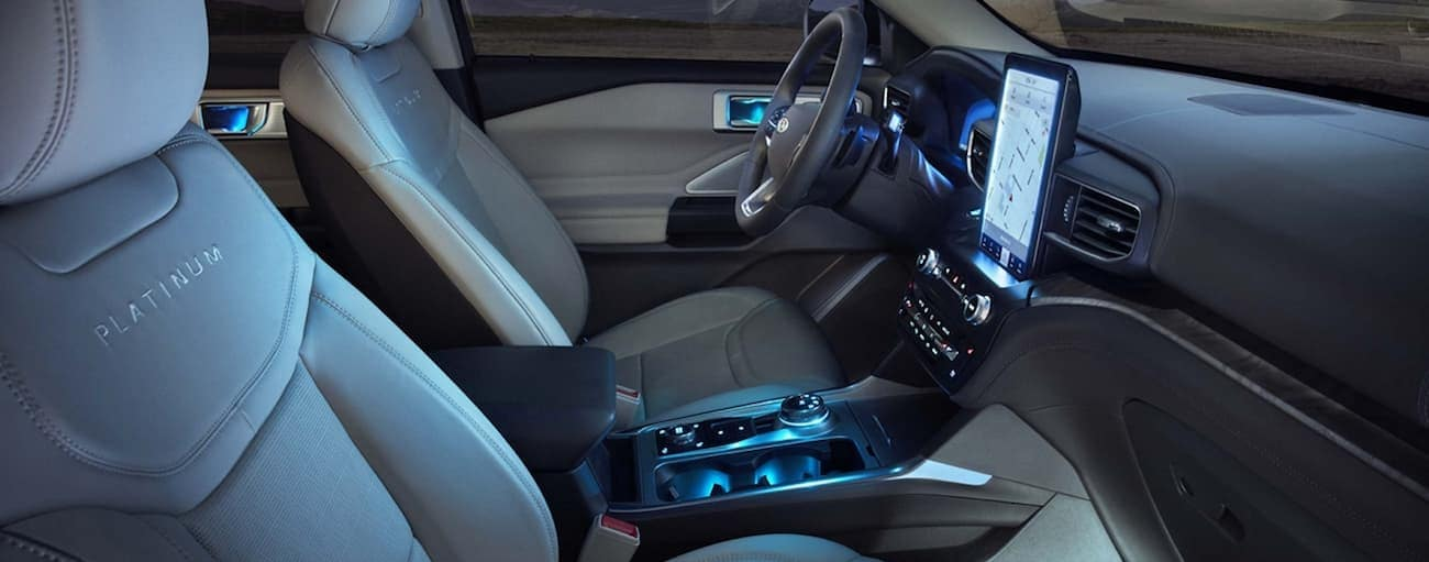 The front tan leather interior of a 2020 Explorer is shown with a large infotinament system.