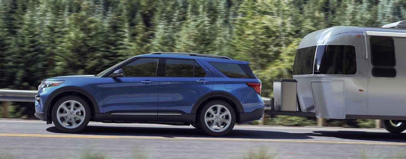 A blue 2020 Ford Explorer, which wins when comparing the 2020 Ford Explorer vs 2020 Chevy Traverse, is towing an Airstream on a treelined road near Albany, NY.