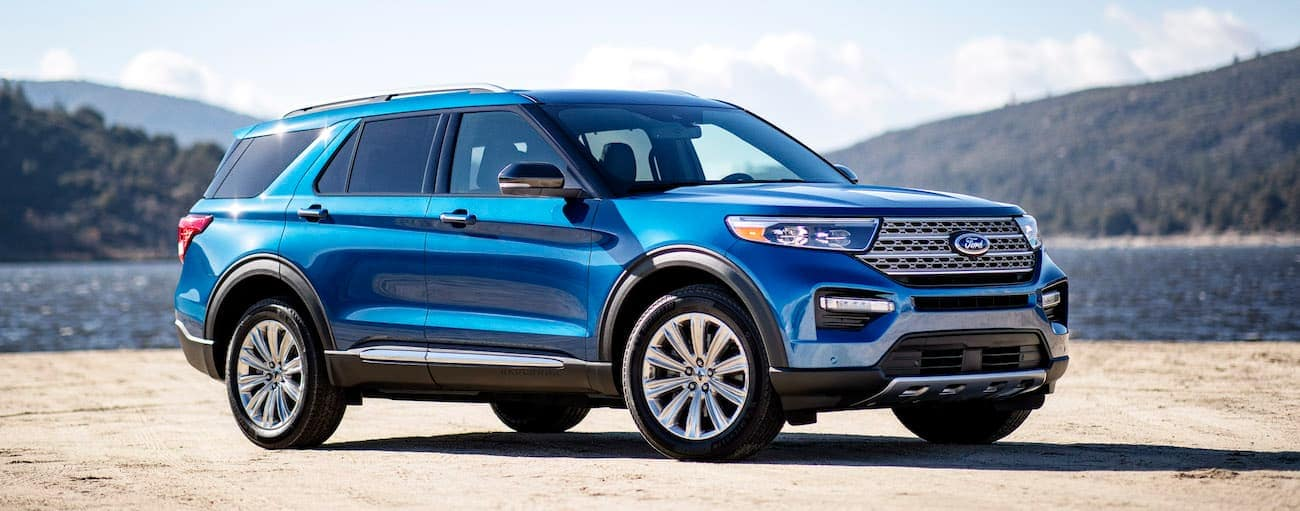A blue 2020 Explorer, which wins when comparing the 2020 Ford Explorer vs 2020 Honda Pilot, is parked in front of a lake near Albany, NY, with trees in the distance.