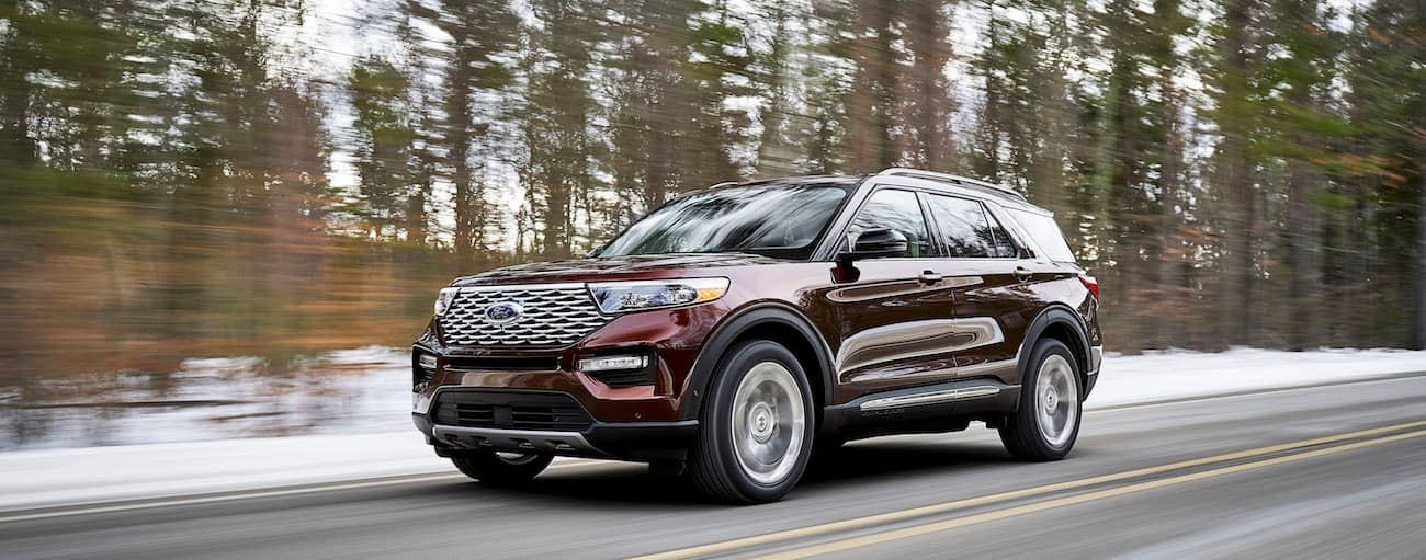 A red 2020 Ford Explorer is driving on a snow lined road near Albany, NY.