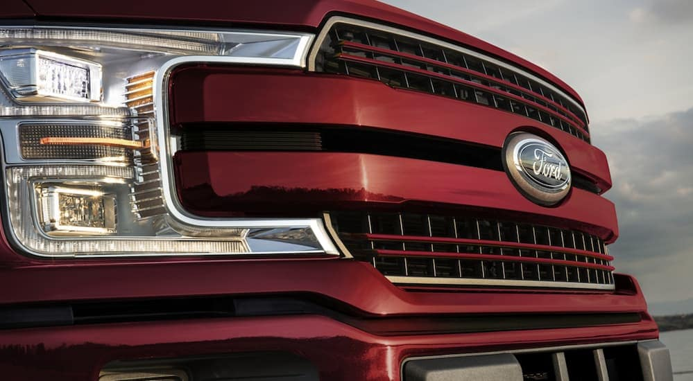 A close up of the front grille of a Ford F-150 is shown in red.