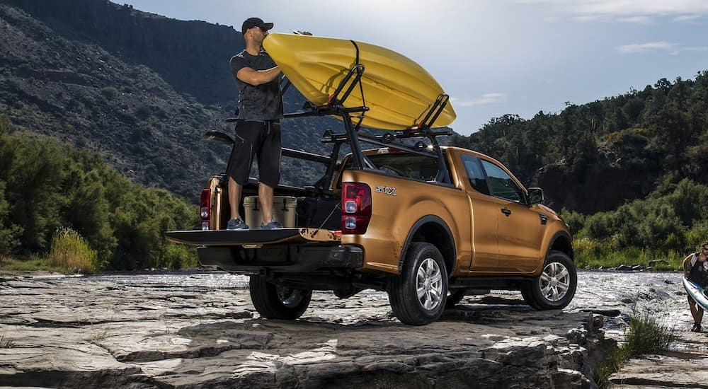 A man is taking his kayak off of the bedrails on his orange 2020 Ford Ranger next to a rocky river.