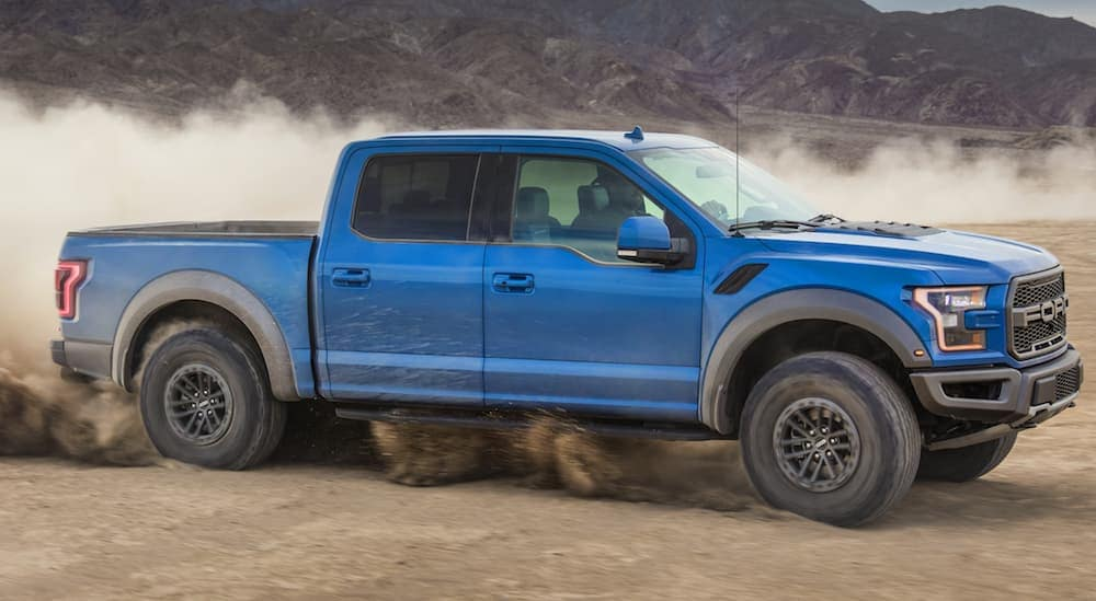 A blue 2020 Ford Raptor is doing donuts in the dirt with mountains in the distance.