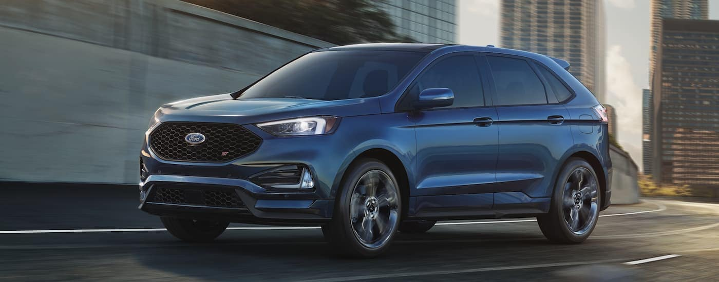 A blue 2020 Ford Edge is driving on a highway with city buildings in the distance.