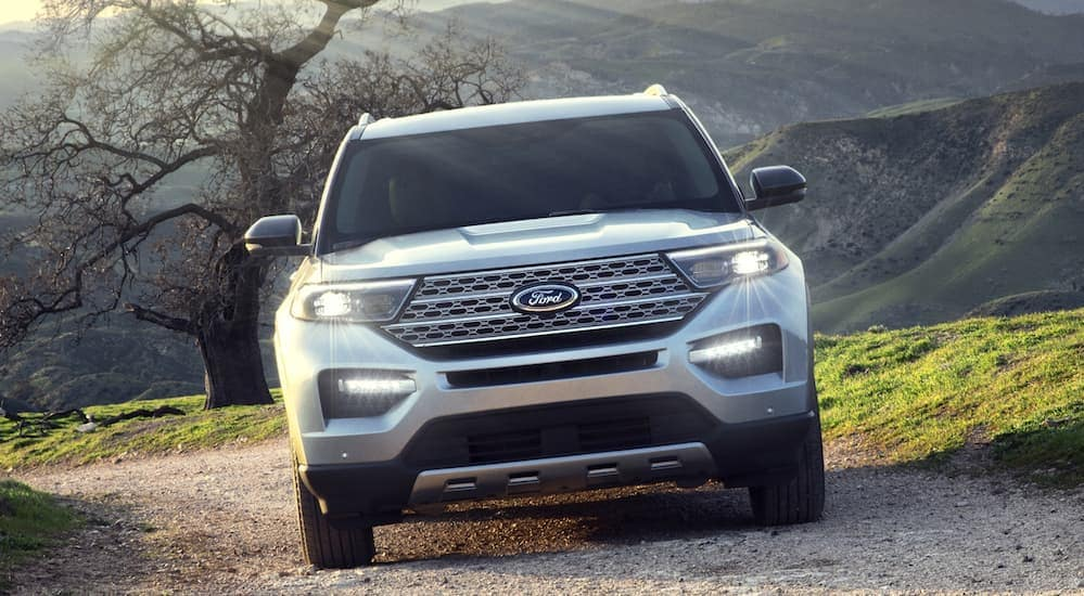 A white 2020 Ford Explorer is driving up a dirt trail that's overlooking tree covered hills near Poughkeepsie, NY.