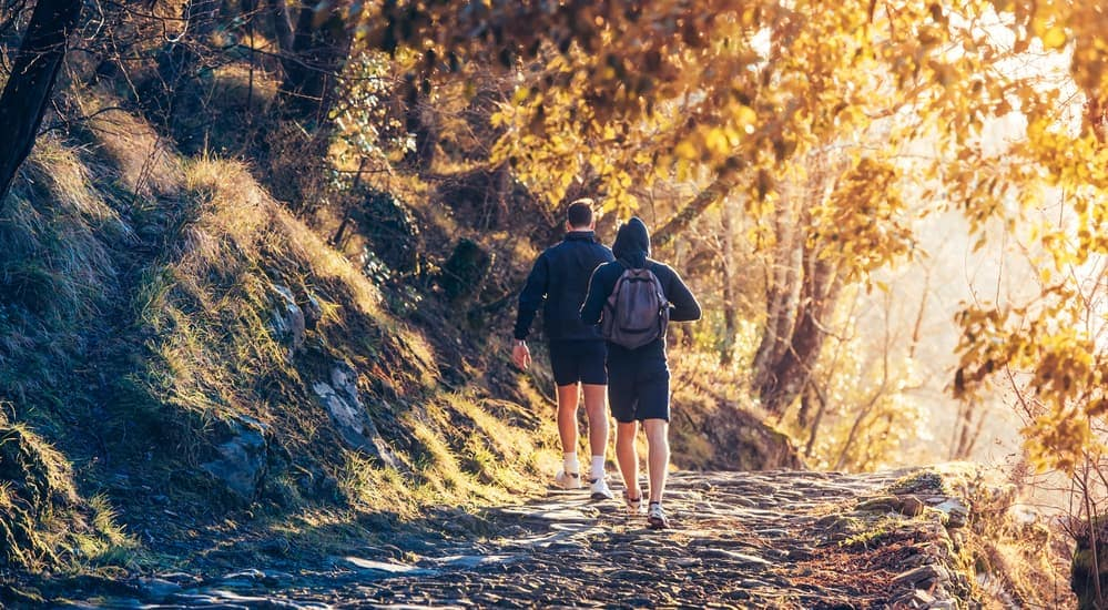 A father and son are hiking on a dirt trail.