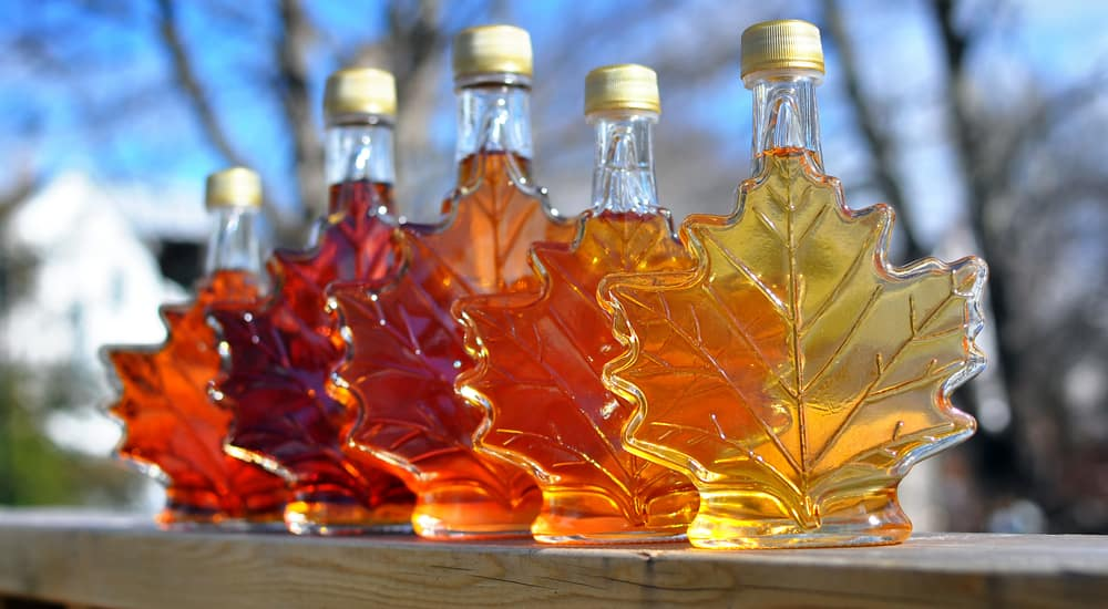 Five maple leaf shaped syrup bottles of different brown colors sitting on a wooden banister