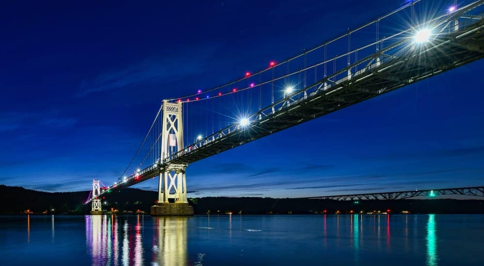 The Mid Hudson Bridge is lit up at night near Poughkeepsie, NY.